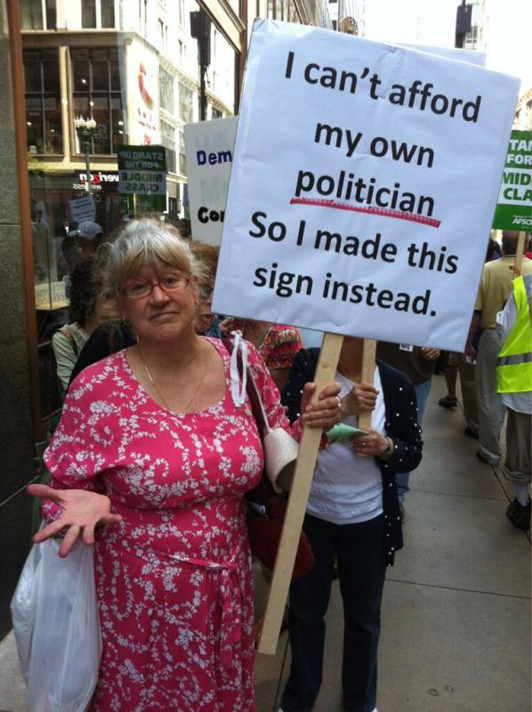 "Woman holding sign ""I can't afford my own politician so I made this sign instead."" (Source: AFSCME Council 30)"