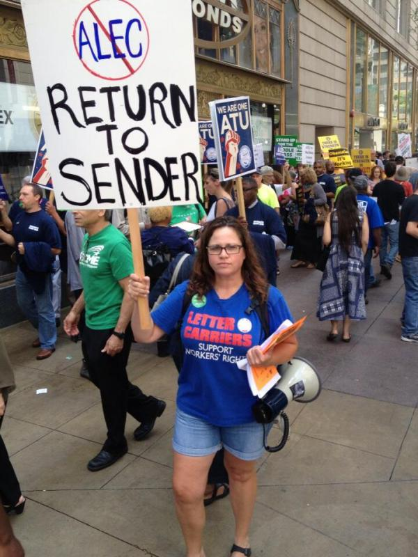 "Woman holding sign with ""No ALEC: Return to Sender"" (Source: Brendan Fischer)"