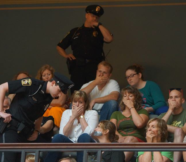 Observers covering their mouths in protest (source: Leslie Peterson)