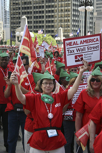 Nurse with sign, robin hood hat and mask (Source: National Nurses United)