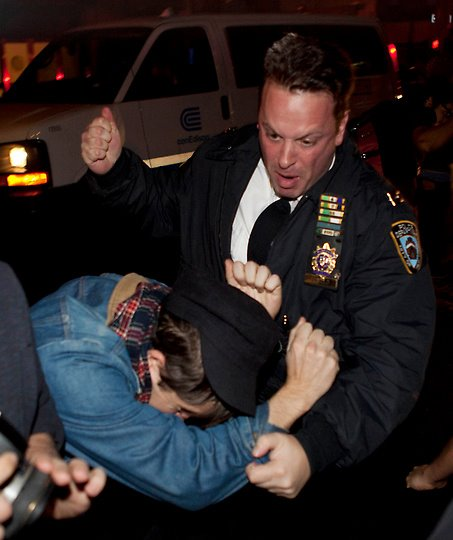A police officer viciously beats an occupier.